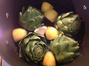 Boil artichokes with quartered lemon.